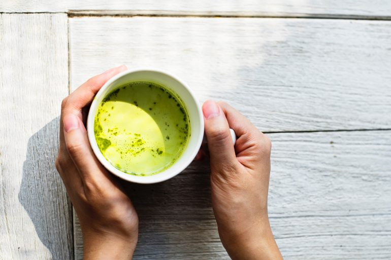 a pair of hands holding a white mug of green tea. credit to rawpixel on unsplash.